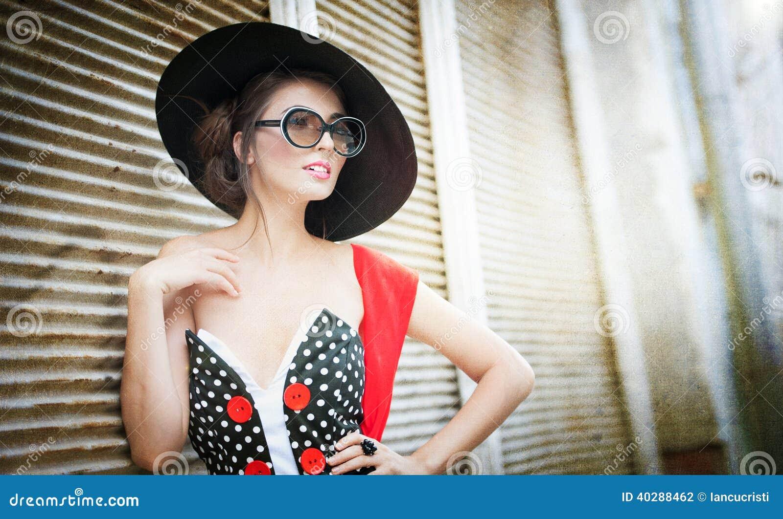 Брюнет с черной шляпой, красным шарфом и представлять солнечных очков внешней