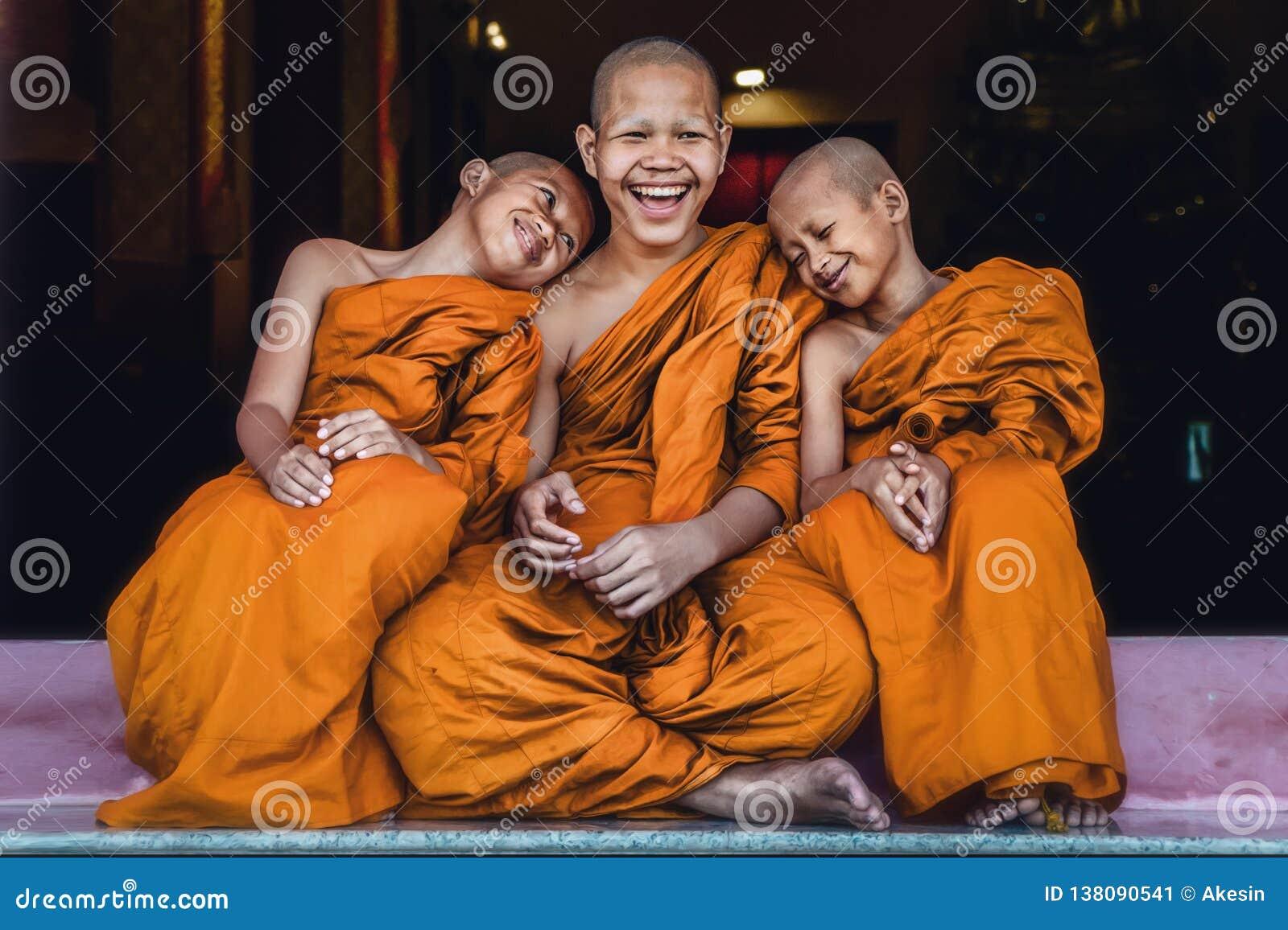Буддийские послушники сидя совместно чувствовать счастливый и улыбка
