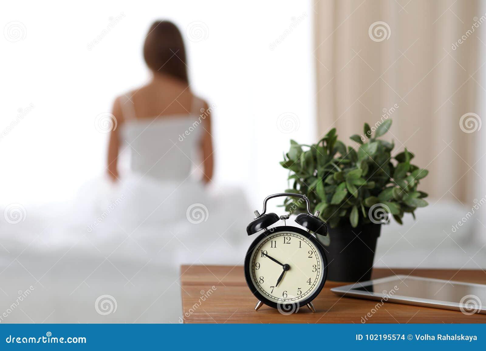 Будильник стоя на прикроватном столике имеет уже звенел рано утром для того чтобы проспать вверх по женщине протягивает в кровати