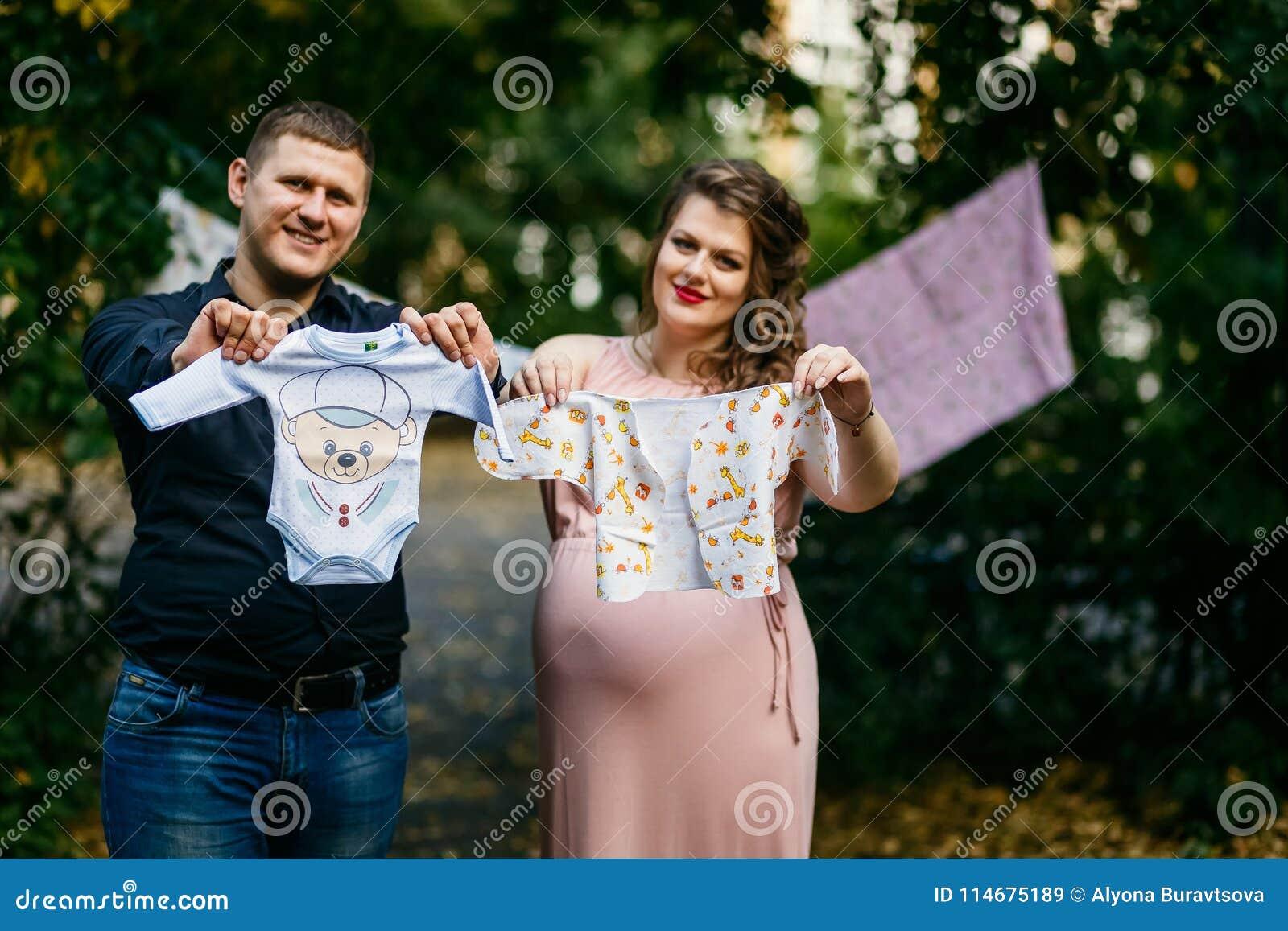 Будущие мама и папа подготавливают одежды младенца для ее нерождённого ребенка