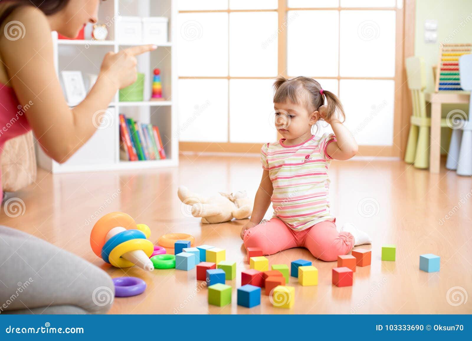 Будьте матерью видеть, что ее дочь играет поднимающее вверх игрушек грязное чувство живущей комнаты сердитое и критикует девушку