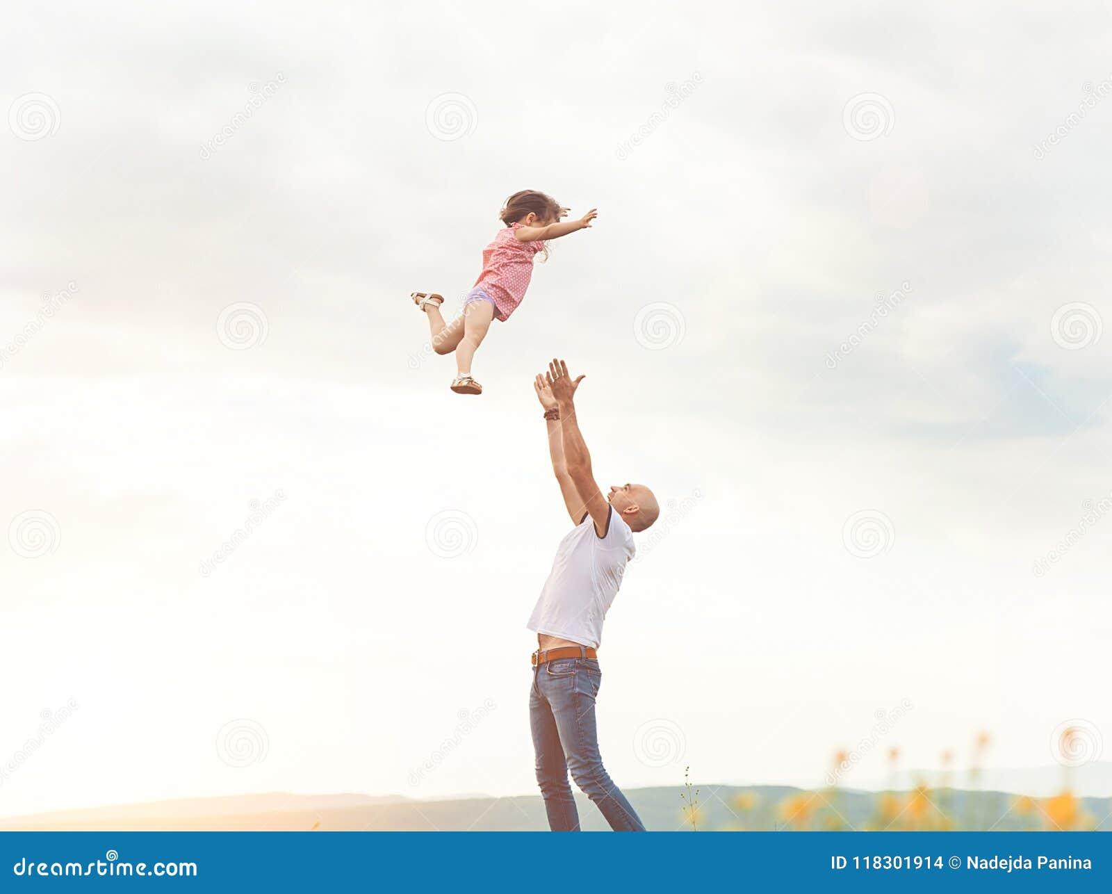 Будьте отцом играть с его дочерью в солнечном поле