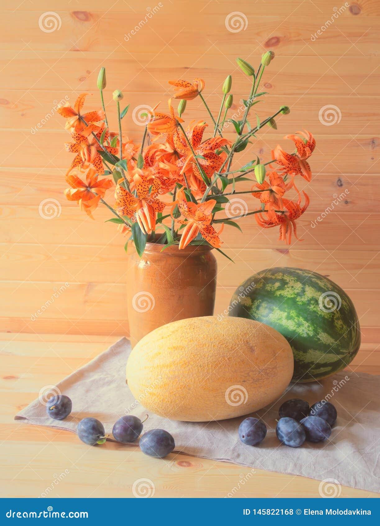 Букет оранжевых лилий, арбуза, дыни и слив близко