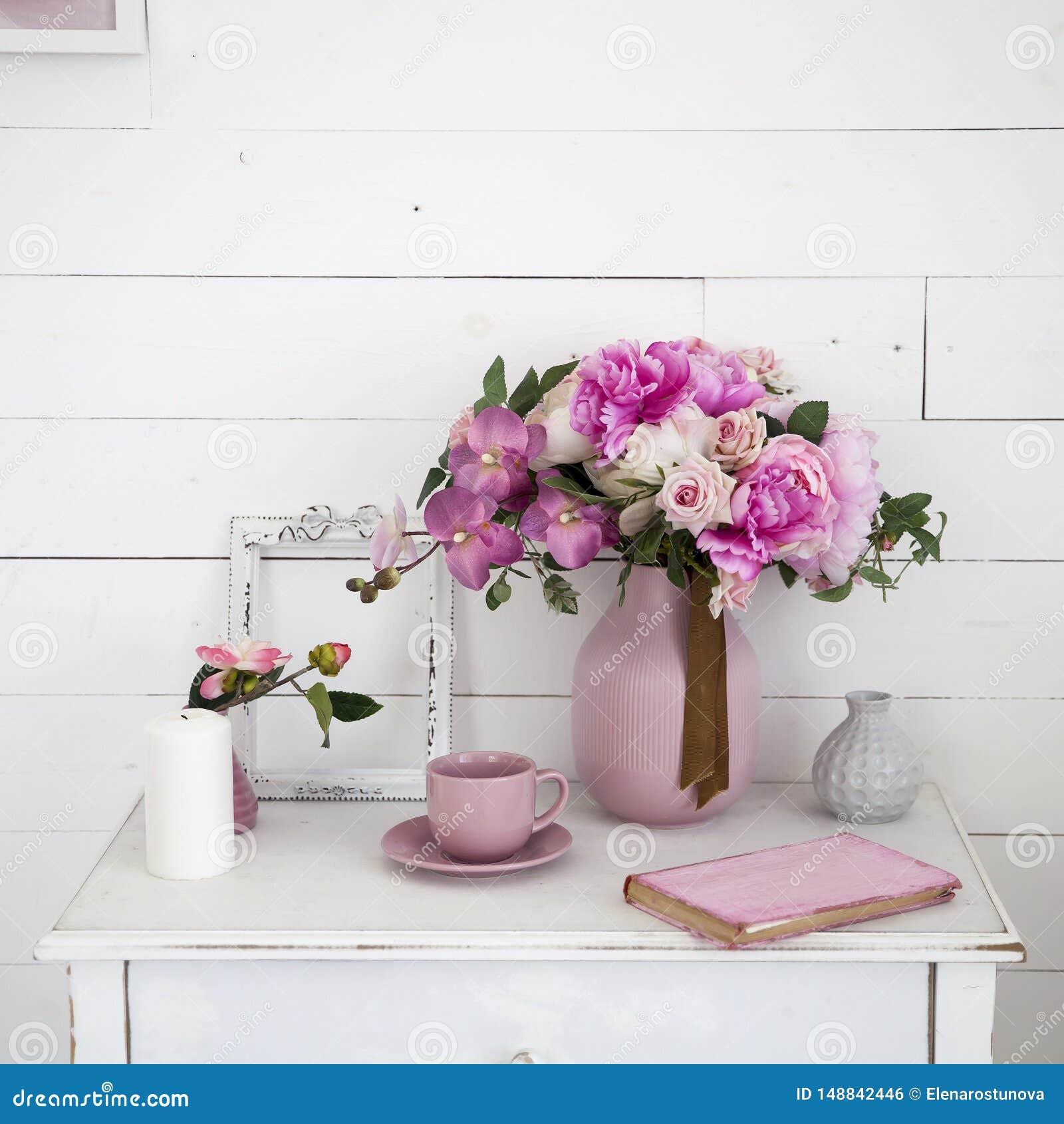 Букет орхидей, пионов, роз в керамической вазе на прикроватном столике и стога книг