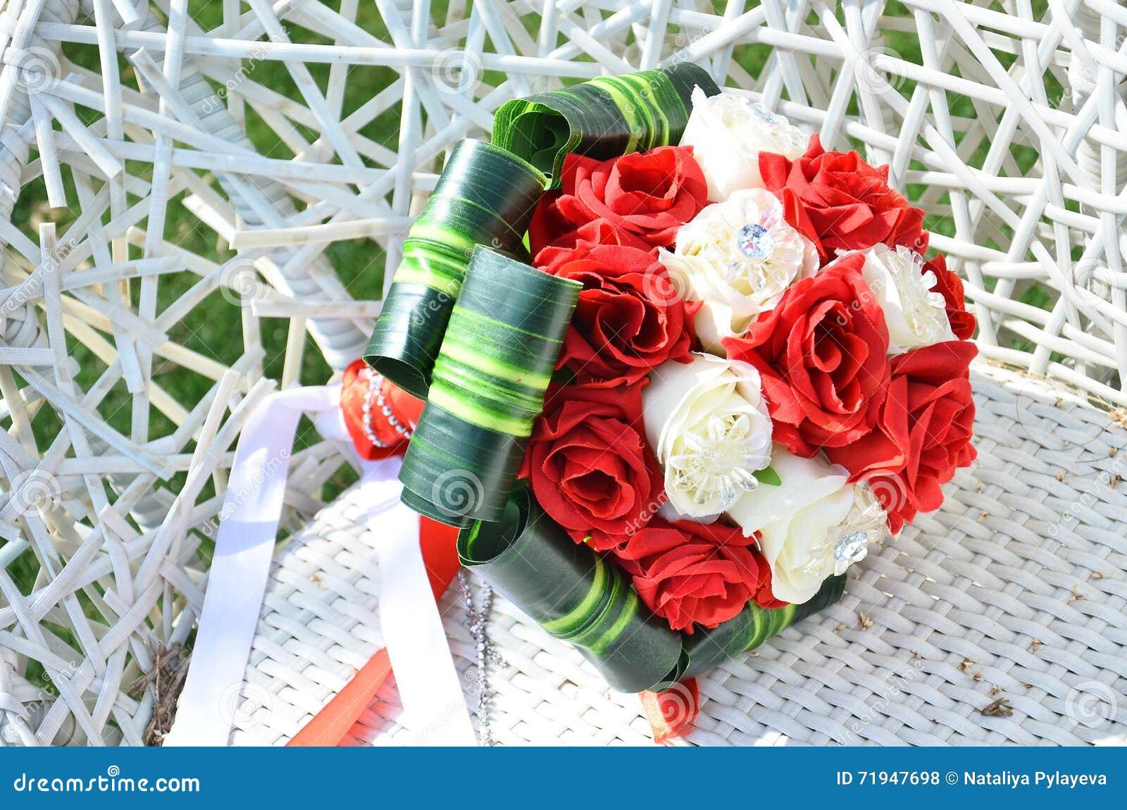 Букет свадьбы роз белизны и шарлаха на плетеном белом стуле
