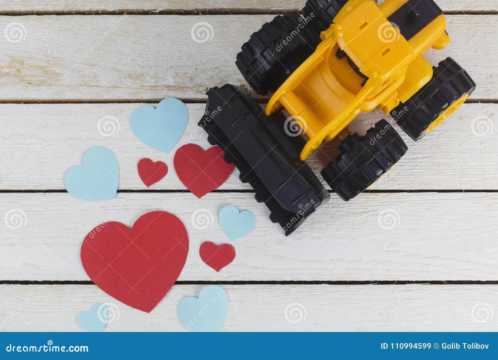 Бульдозер игрушки собирает бумажные сердца