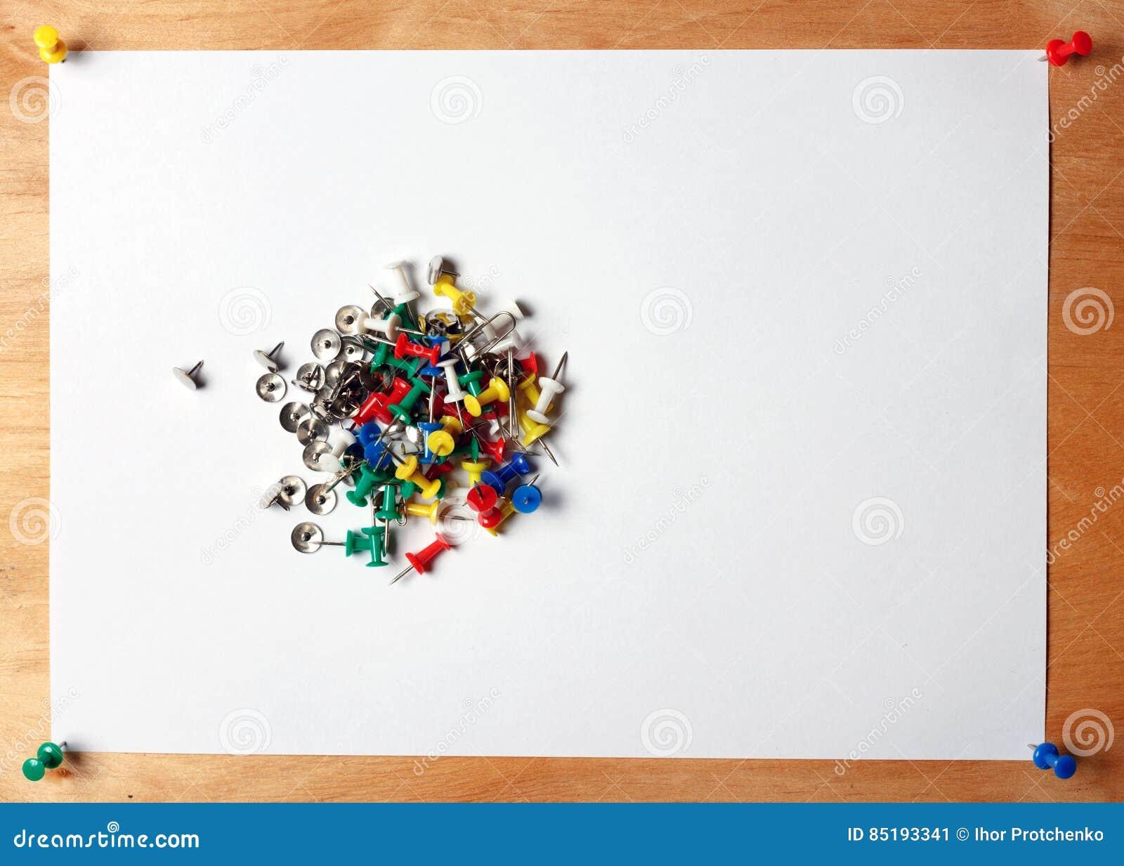 Бумага и много красят канцелярские кнопки красный, голубой, зеленый, желтый, белый Лист прикрепленный к деревянной доске