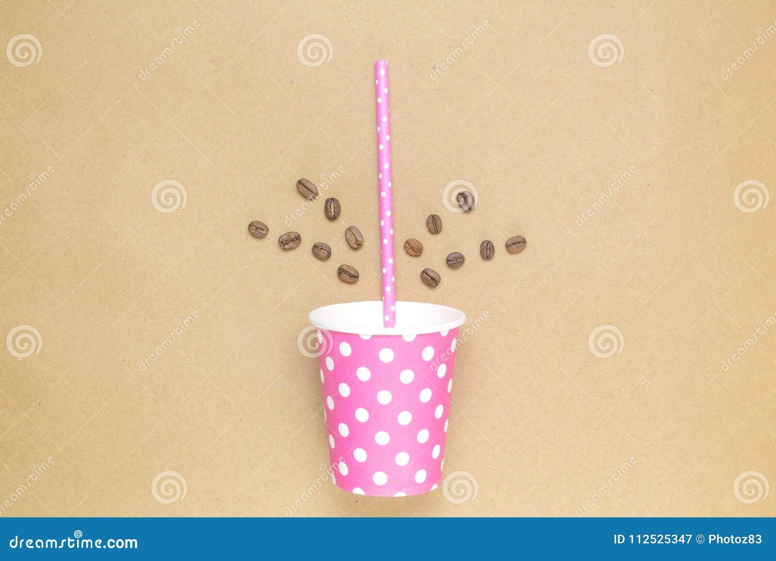 Бумажная кофейная чашка с выпивая соломой и кофейными зернами