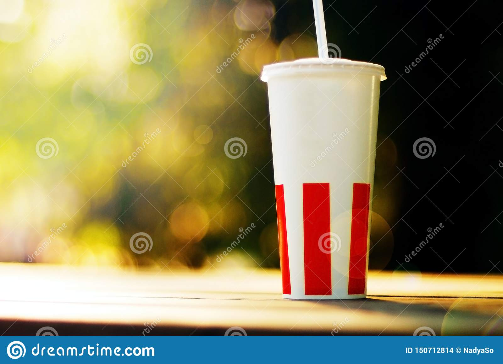 Бумажный стаканчик с соломой и положение на деревянной скамейке в парке, зеленой предпосылке bokeh, солнечности