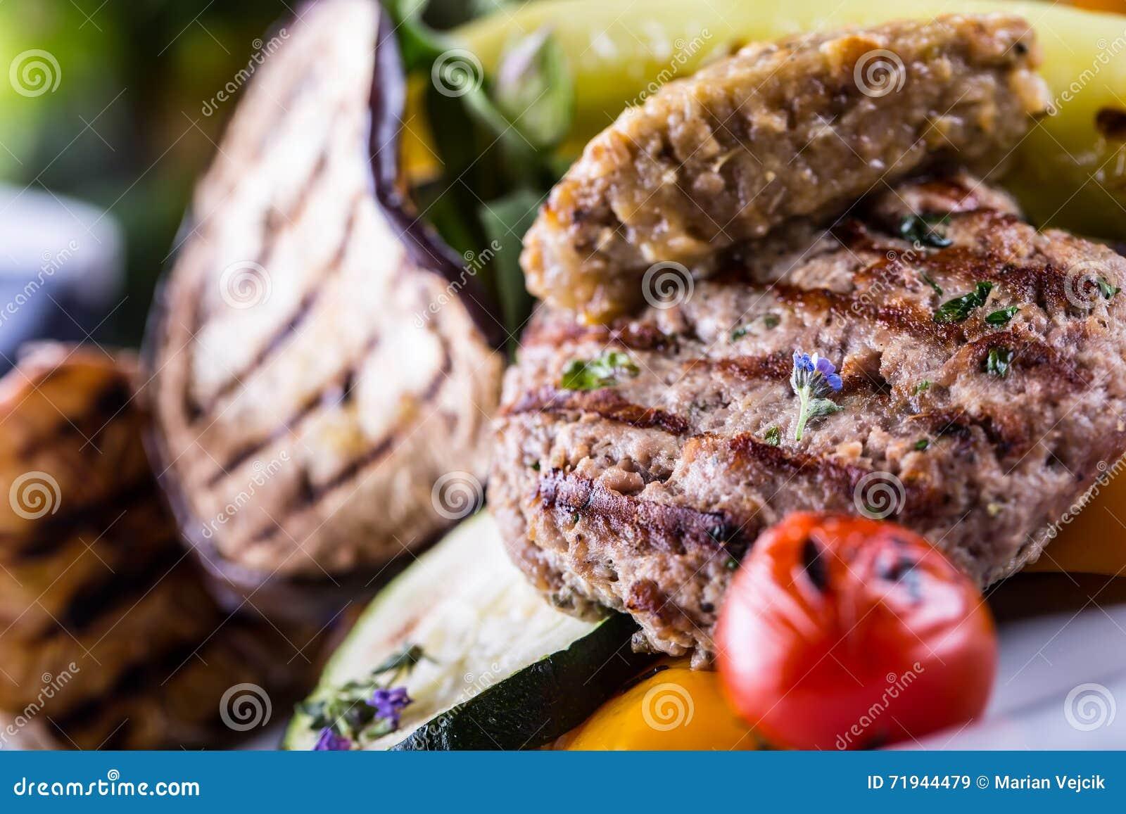 Бургеры Бургеры гриля Семенить бургеры Зажаренные в духовке бургеры с зажаренным украшением овоща и травы Семенить мясо зажаренно