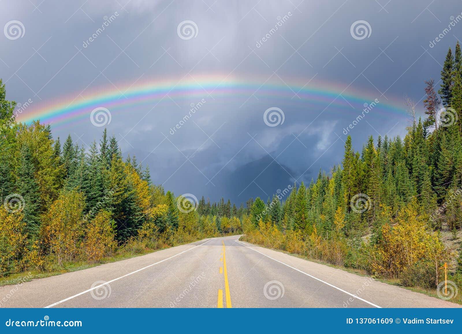 Бурное небо и радуга над пустым шоссе 93 асфальта альбатроса Канада