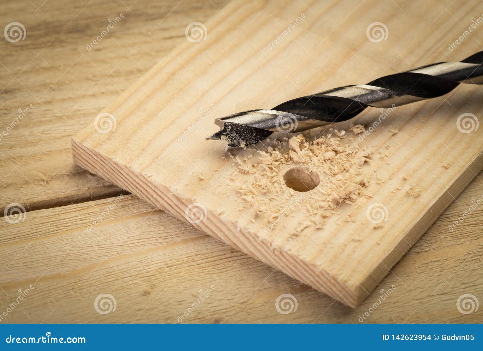 Буровые наконечники металла на деревянной предпосылке Diy дома