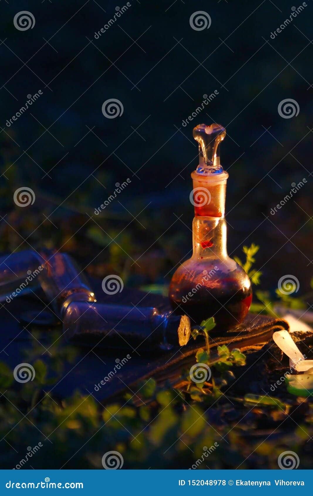 Бутылка зелья на предпосылке волшебных ингредиентов