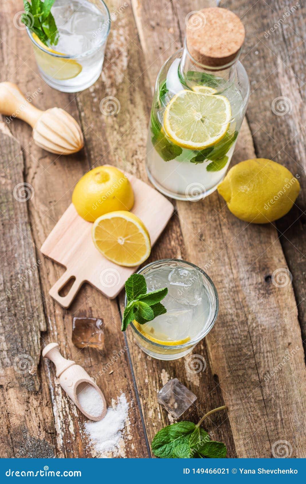 Бутылка и 2 стекла свежего лимонада с кусками, мятой и льдом лимона на старых деревянных планках