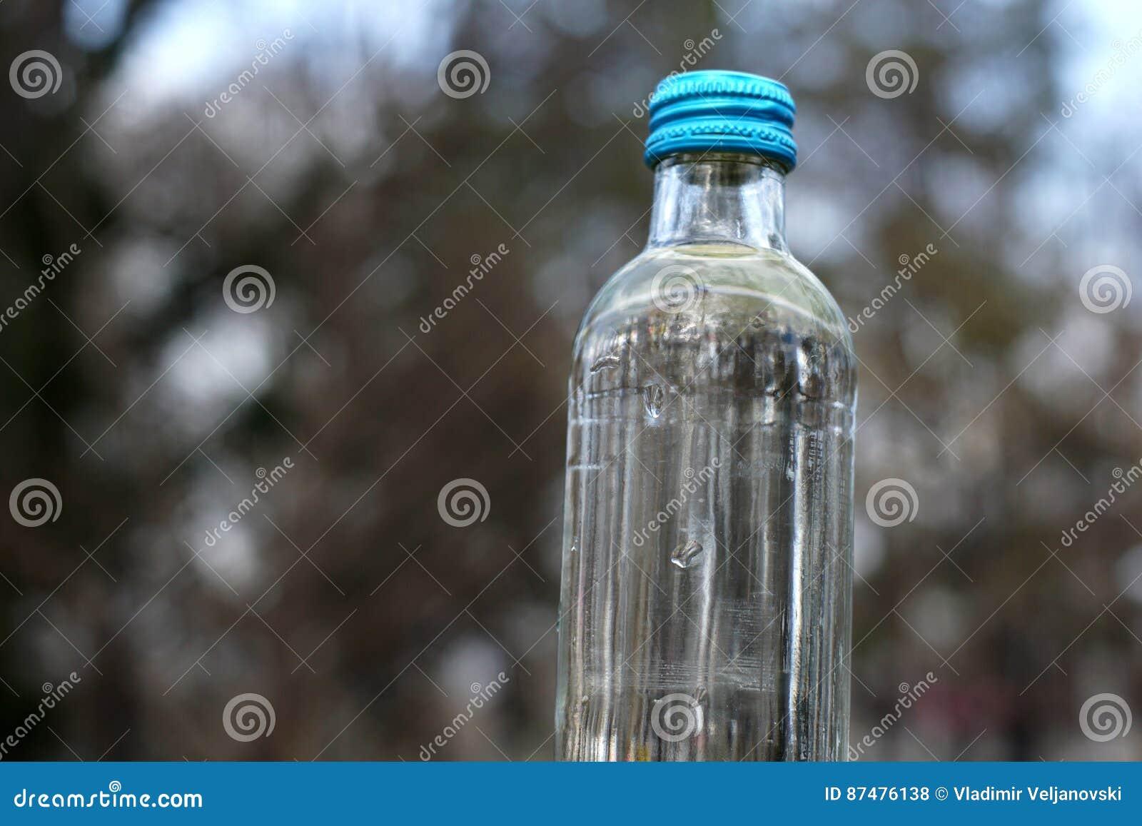 Бутылка с водой на предпосылке запачканных деревьев