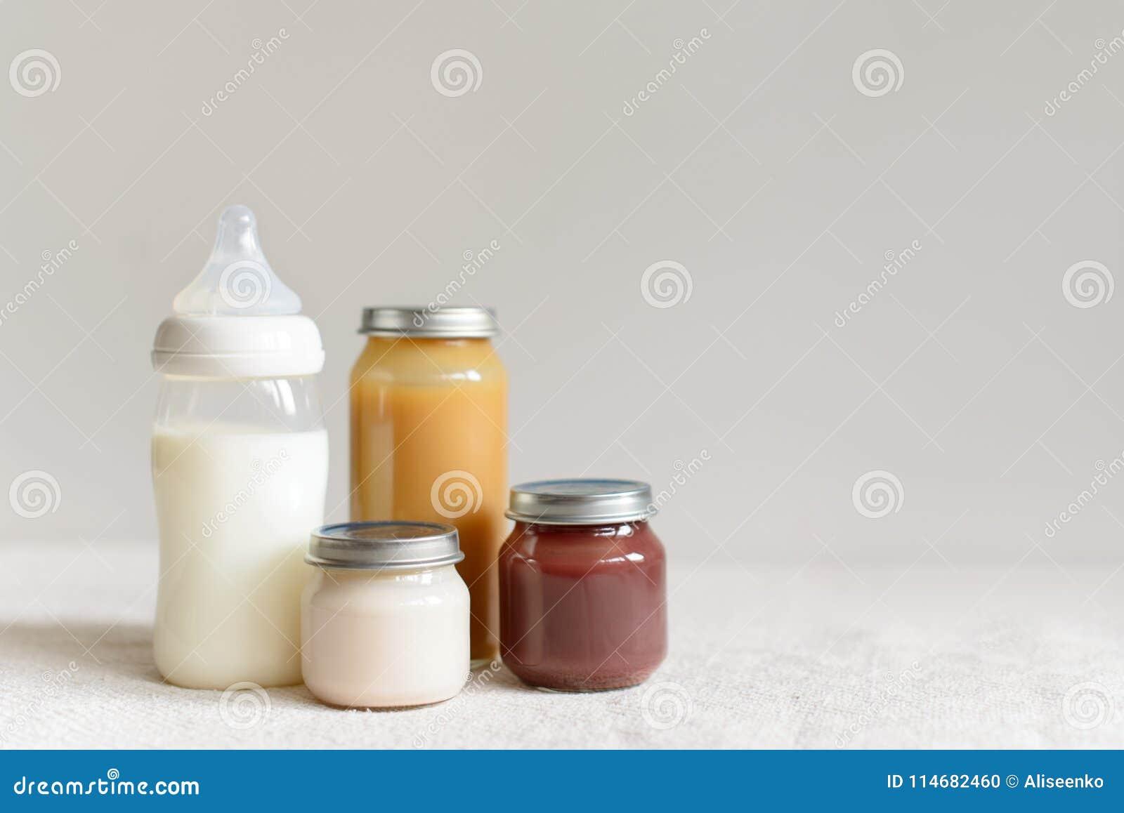 Бутылки молока и пюра для младенца над запачканной предпосылкой