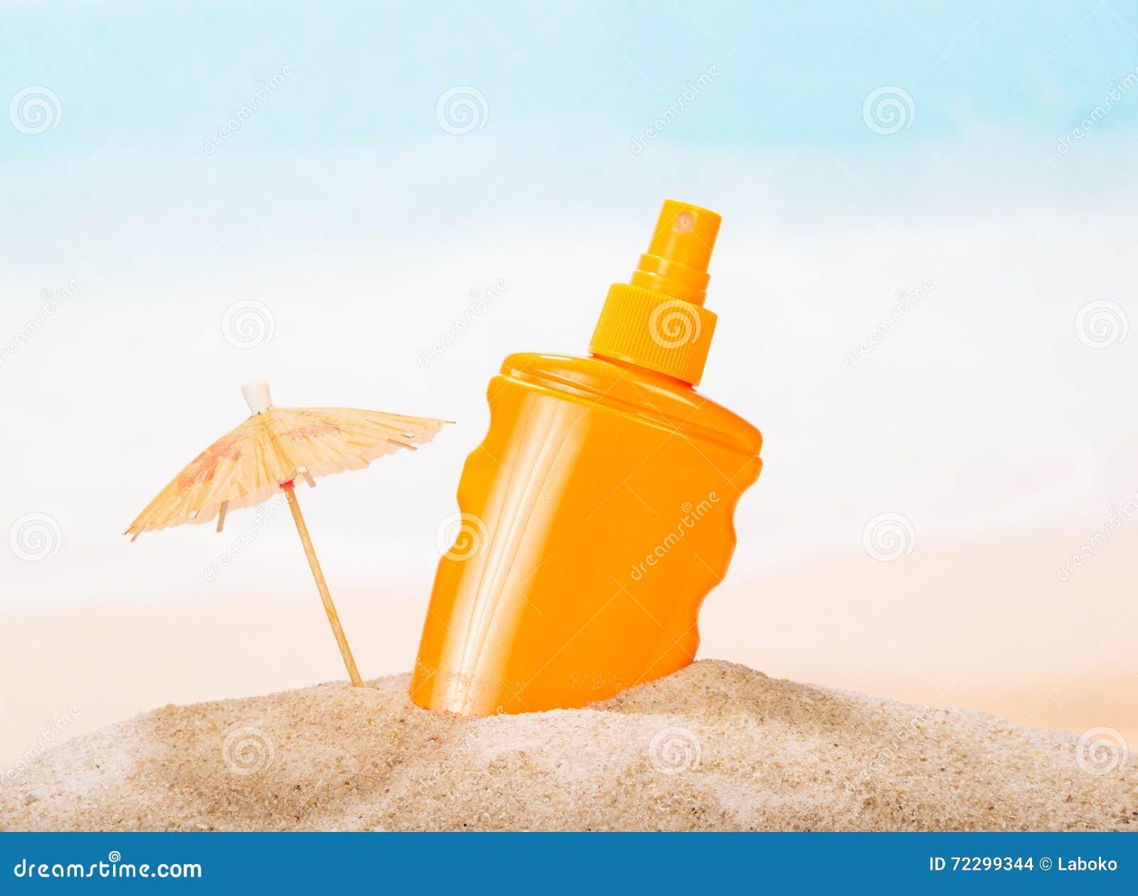 Download Бутылка солнцезащитного крема в песке против моря Стоковое Фото - изображение насчитывающей sunbathing, песок: 72299344