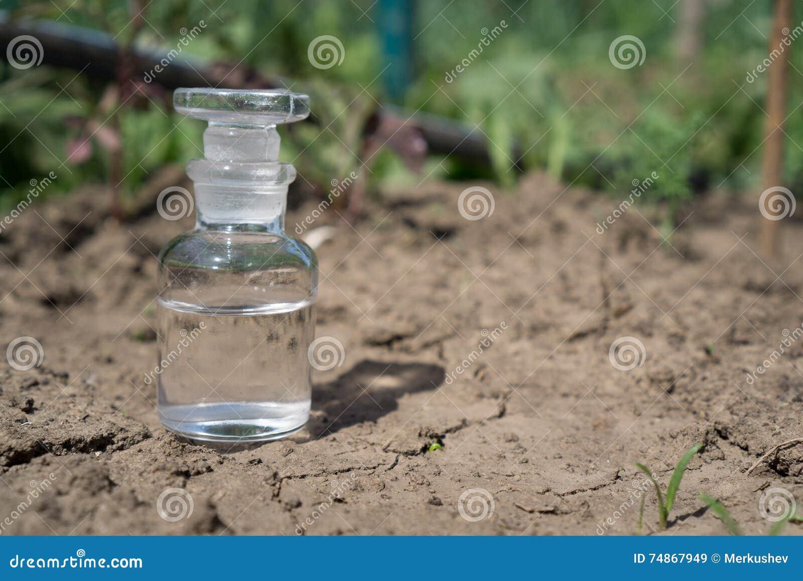 Бутылка с водой или удобрением на сухой треснутой почве ...
