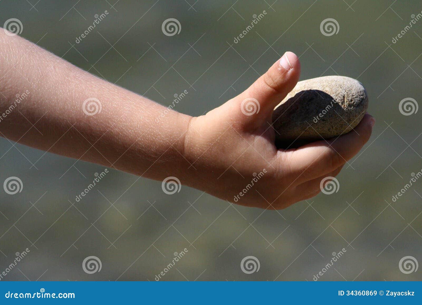 Булыжник, который держат в правой руке ребенка