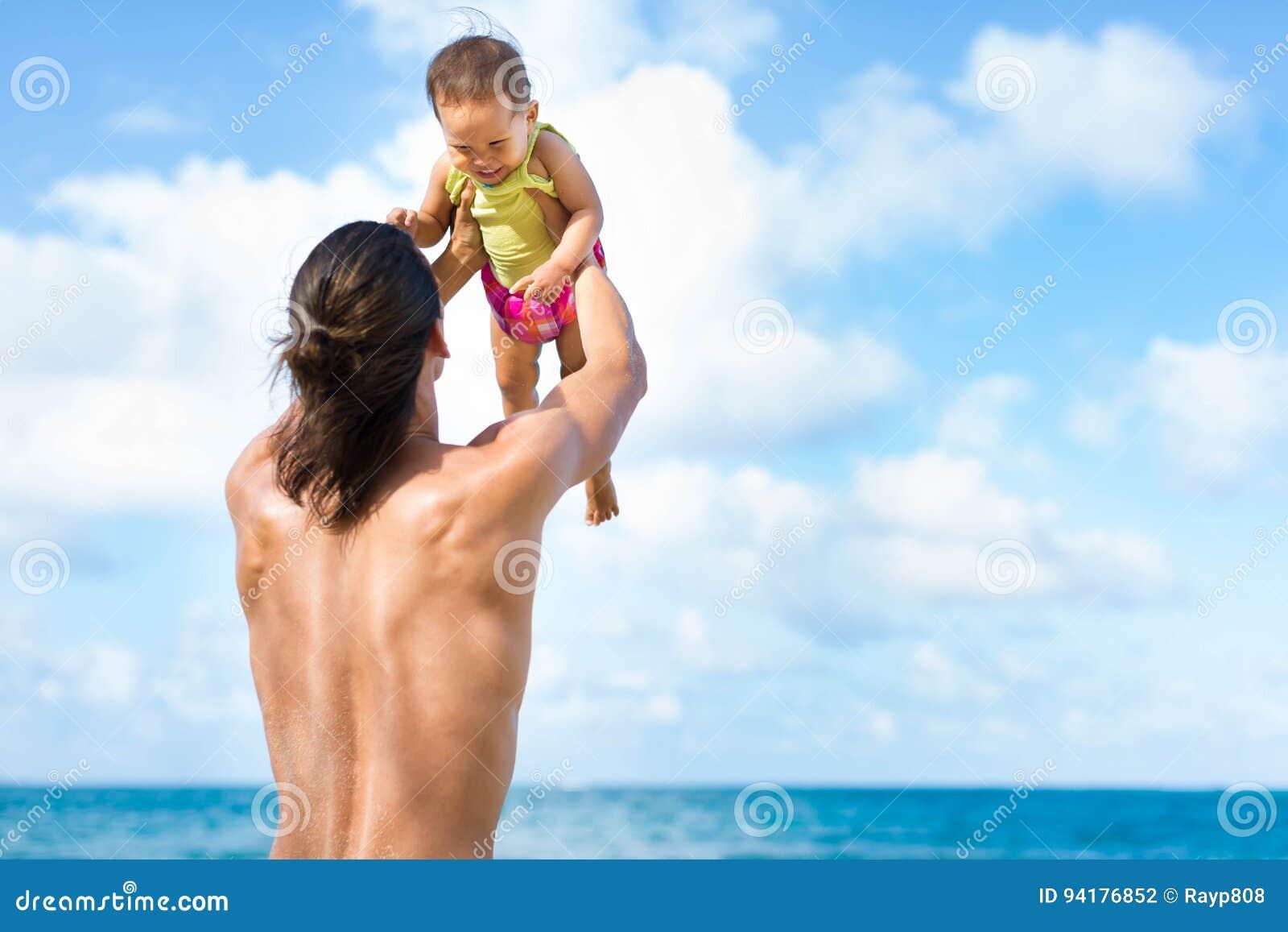 Будьте отцом метать его ребенок шаловливо на пляже