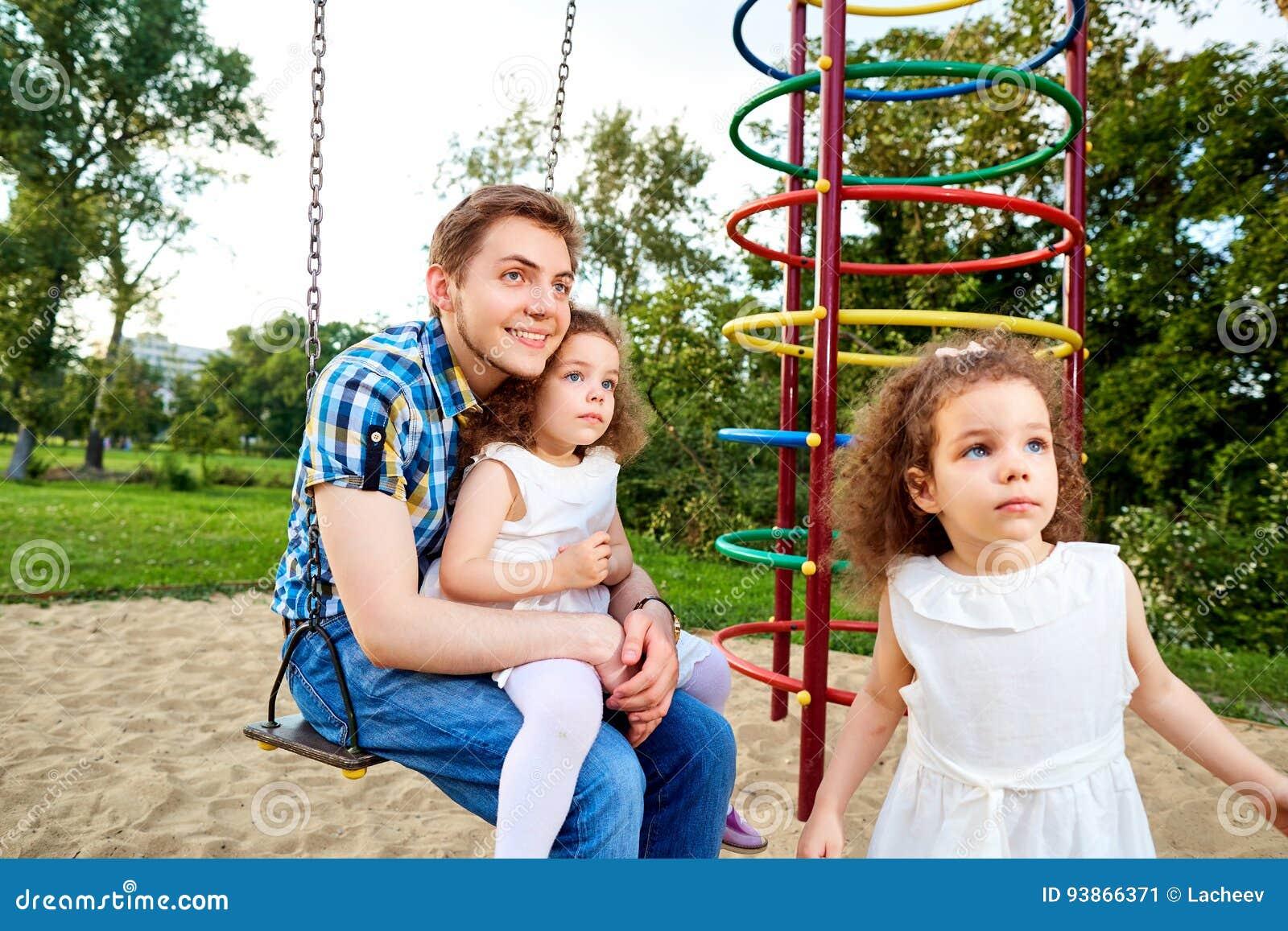 Будьте отцом с детьми на качании на спортивной площадке