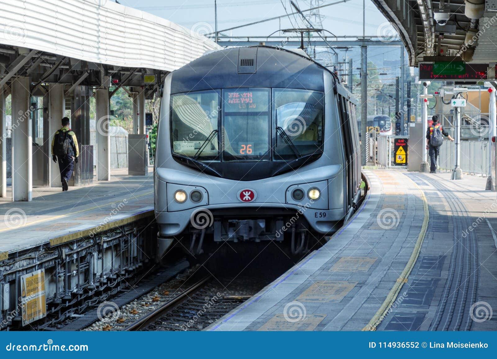 Быстрый поезд метро приезжает на под открытым небом станцию, людей идет на платформу MTR Корпорация