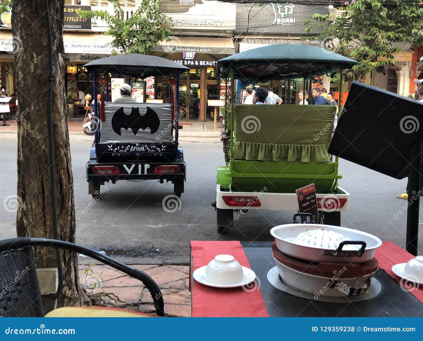 Бэтмэн Tuk Tuk VIP черноты Камбоджи Siem Reap припарковано рядом с зеленым цветом одним на главной улице
