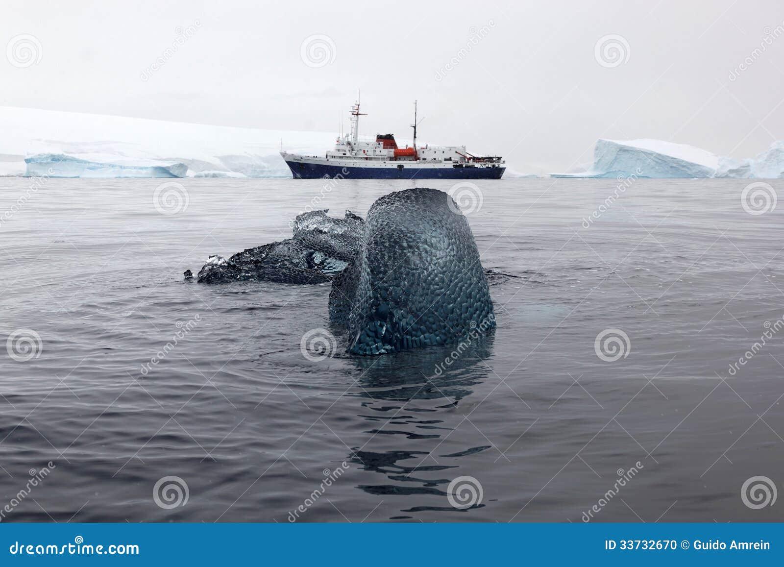 Блок черного льда с шлюпкой исследования на заднем плане, Антарктика