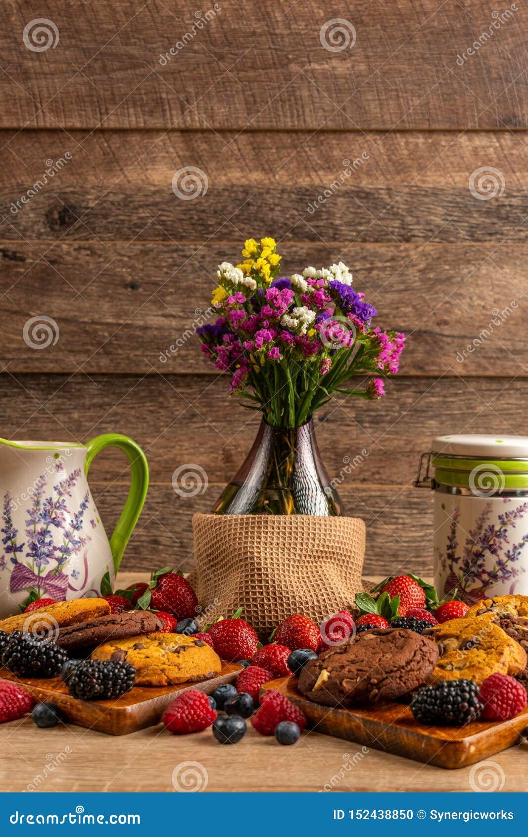 Ваза цветка, керамические сосуды с сортированным смешиванием диких плодов и печенья