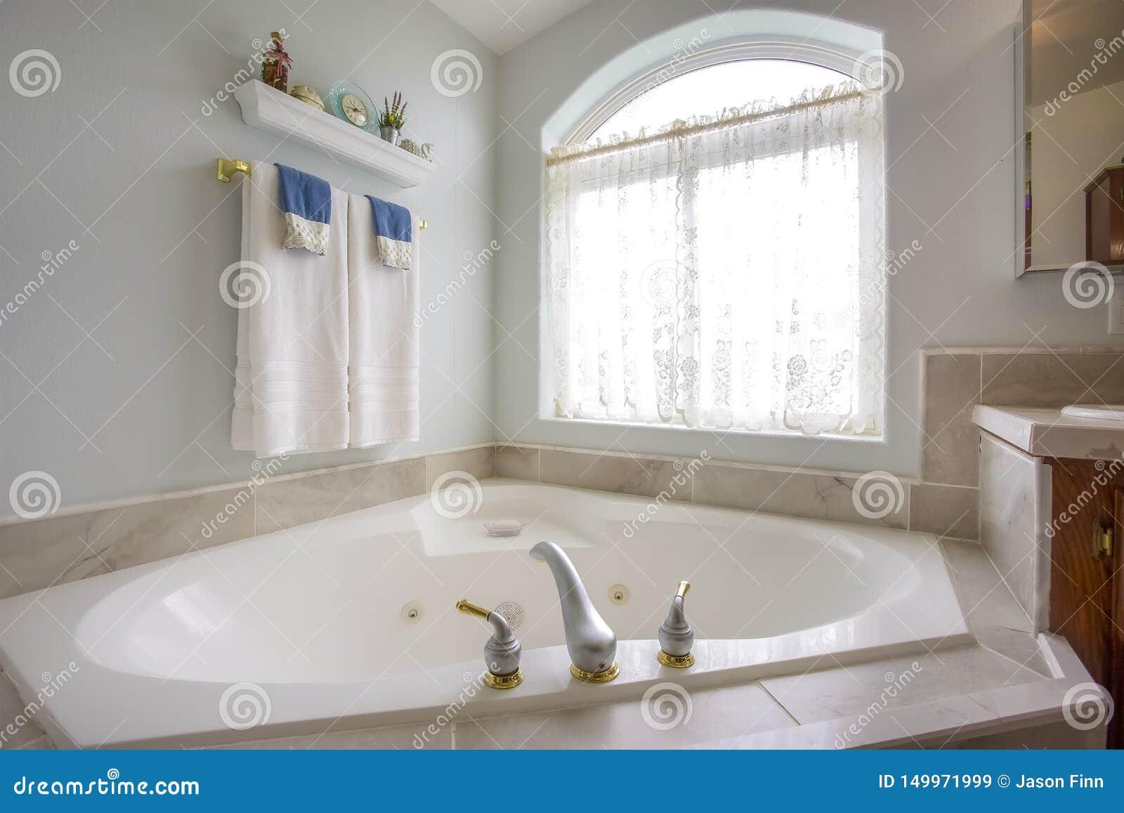 Ванна с с золотом и серебряным faucet около сдобренного окна с занавесом