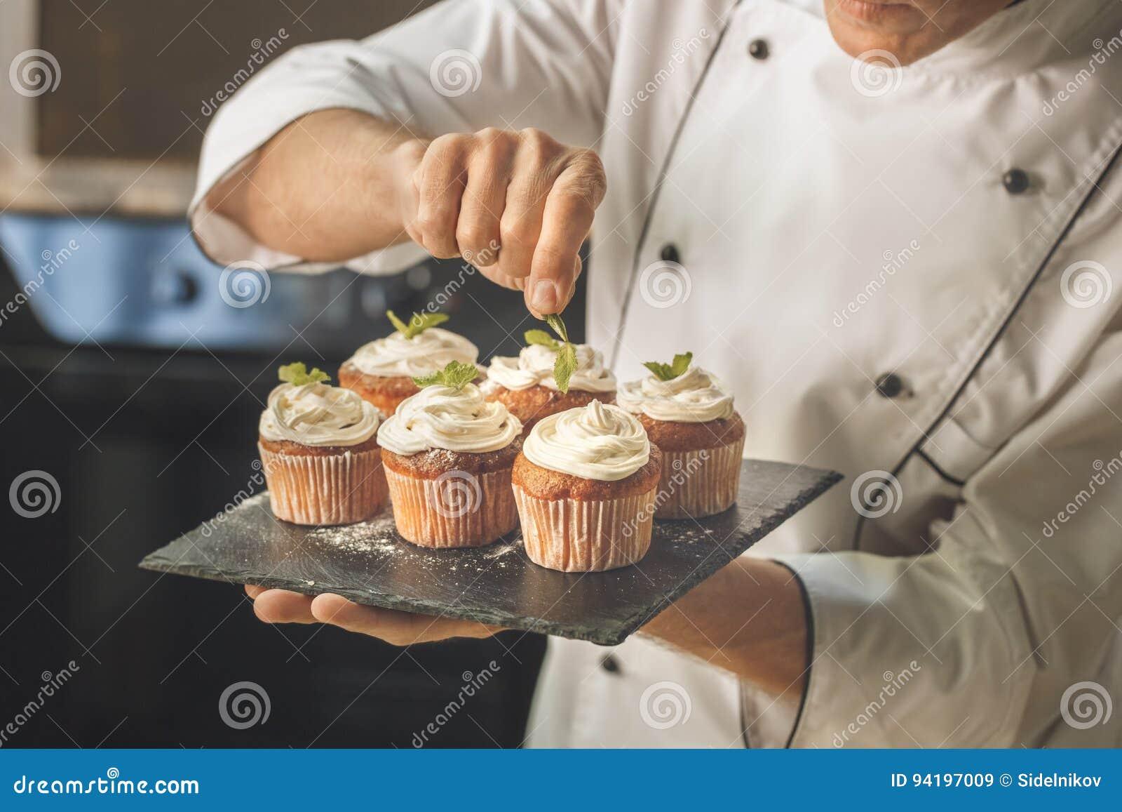 Варить шеф-повара хлебопекарни печет в профессионале кухни