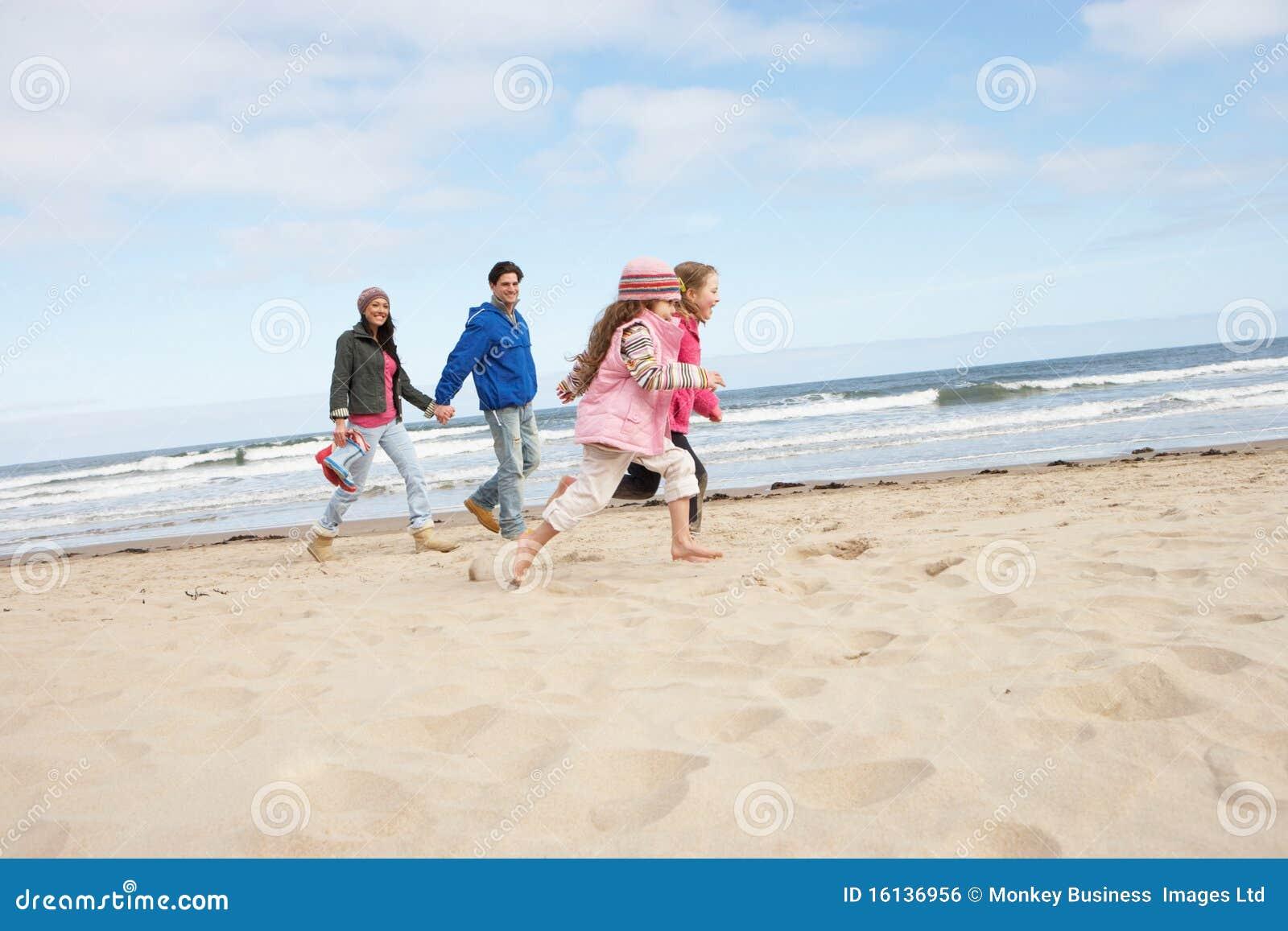 вдоль зимы семьи пляжа гуляя