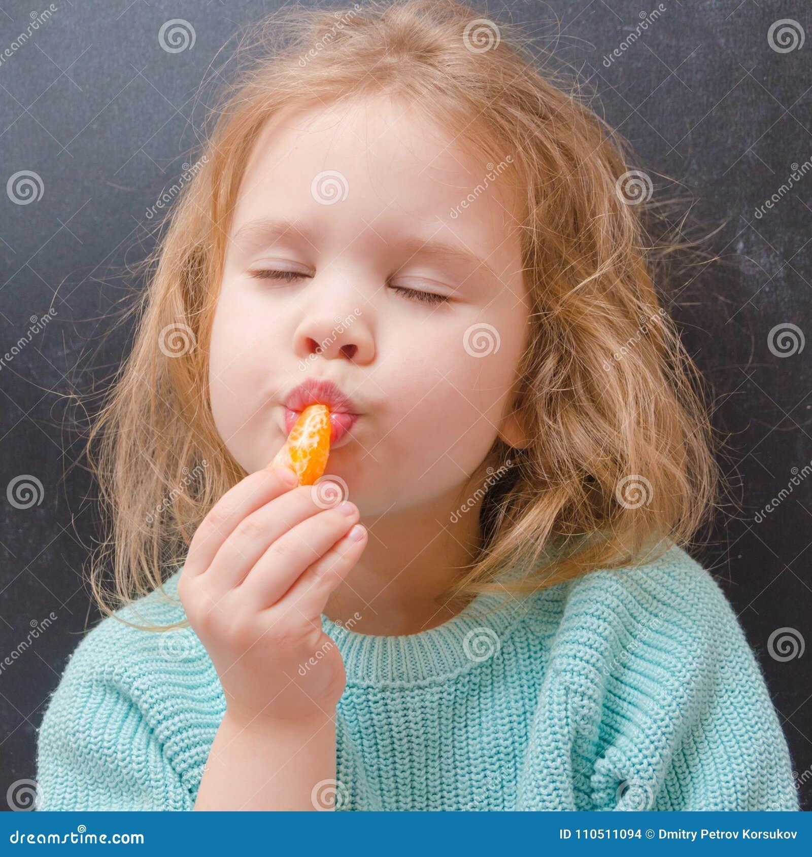 Вегетарианец ребёнка с куском мандарина