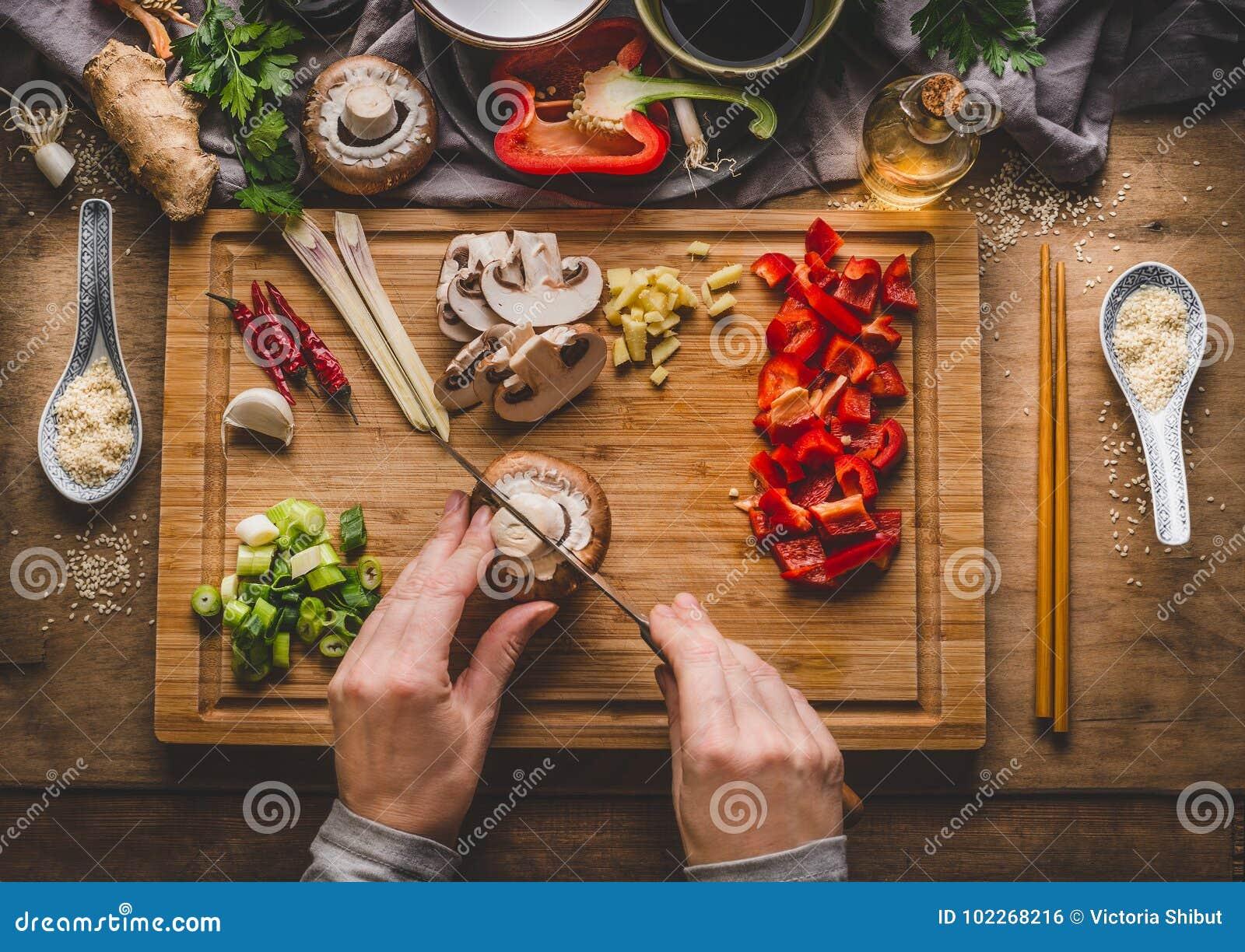 Вегетарианский фрай stir варя подготовку Женщины женские руки режут овощи для фрая stir на предпосылке кухонного стола с ingredie
