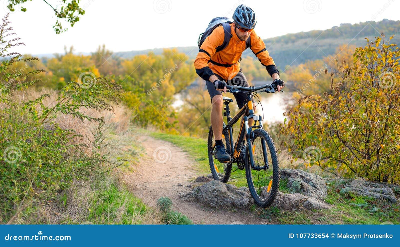 Велосипедист в апельсине ехать горный велосипед на следе осени скалистом Весьма спорт и концепция Enduro велосипед