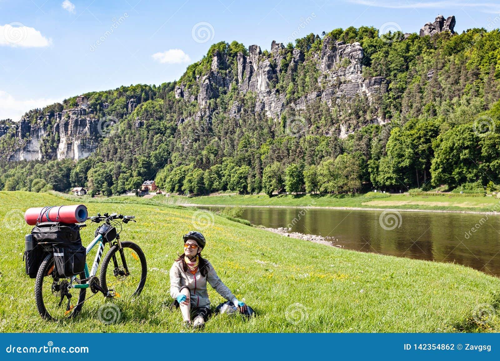 Велосипедист женщины с нагруженным велосипедом имея перерыв пока путешествующ