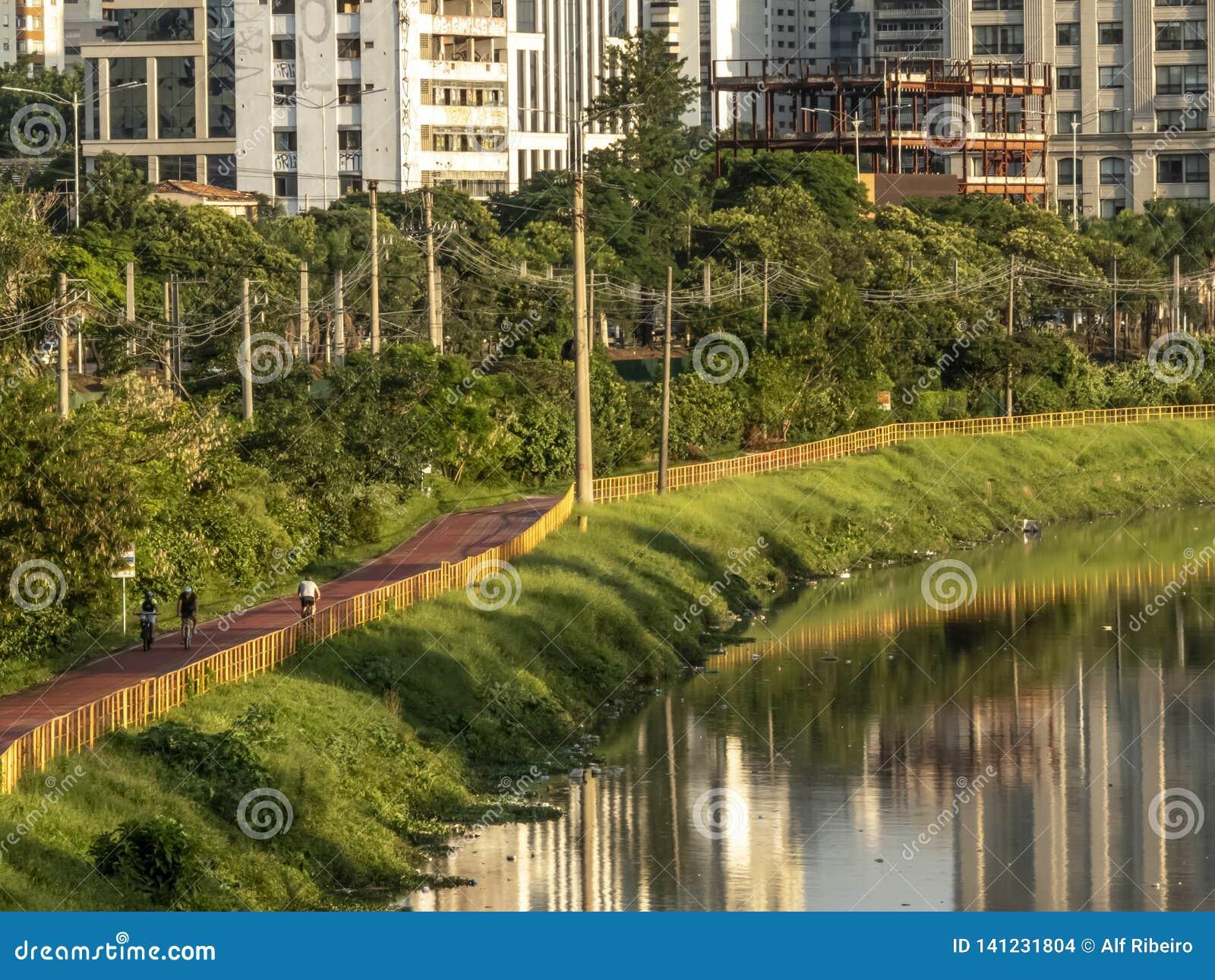 Велосипедист на майне велосипеда близко реки Pinheiros, западной стороны Сан-Паулу