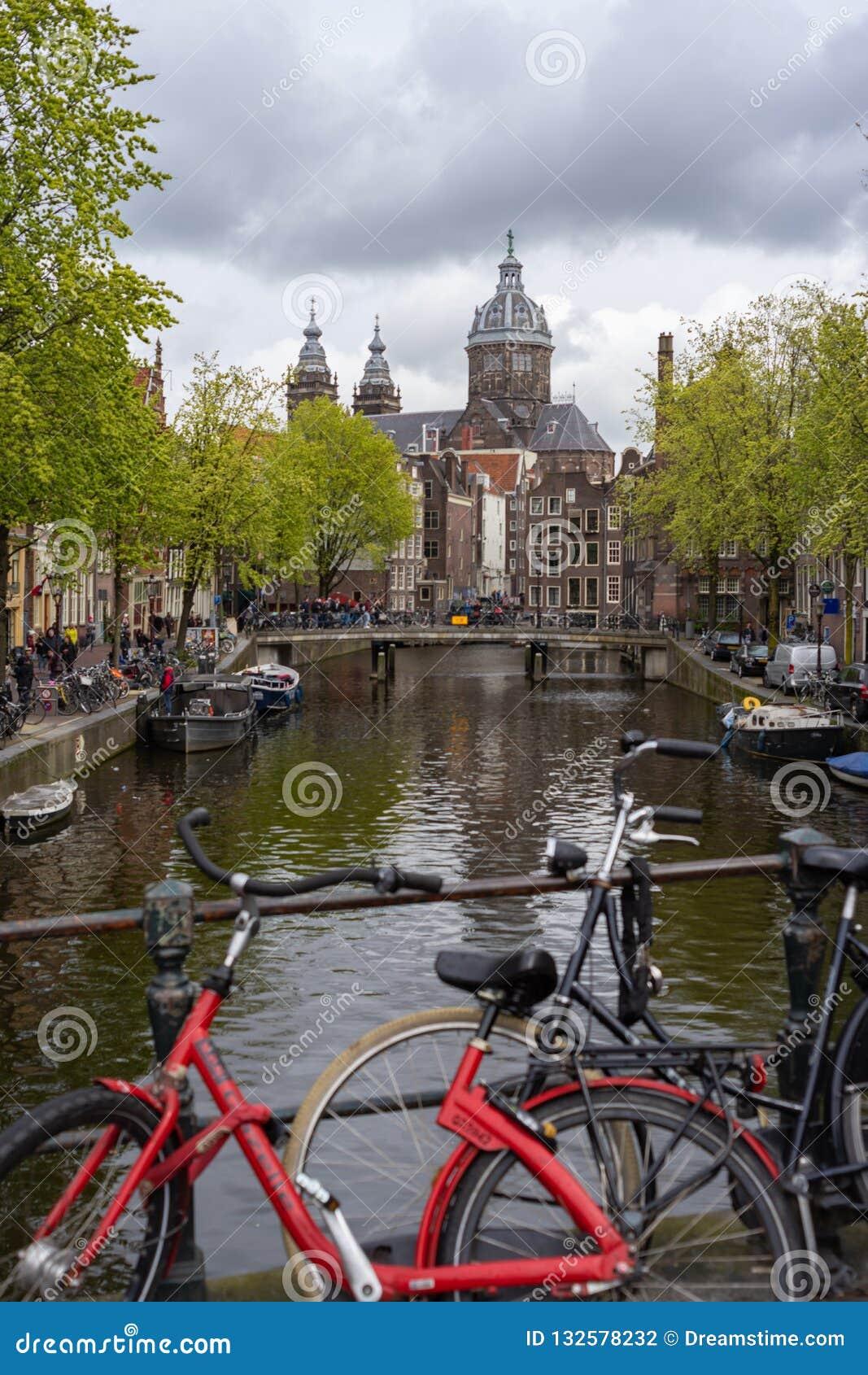 Велосипеды за мостом в канале Амстердама