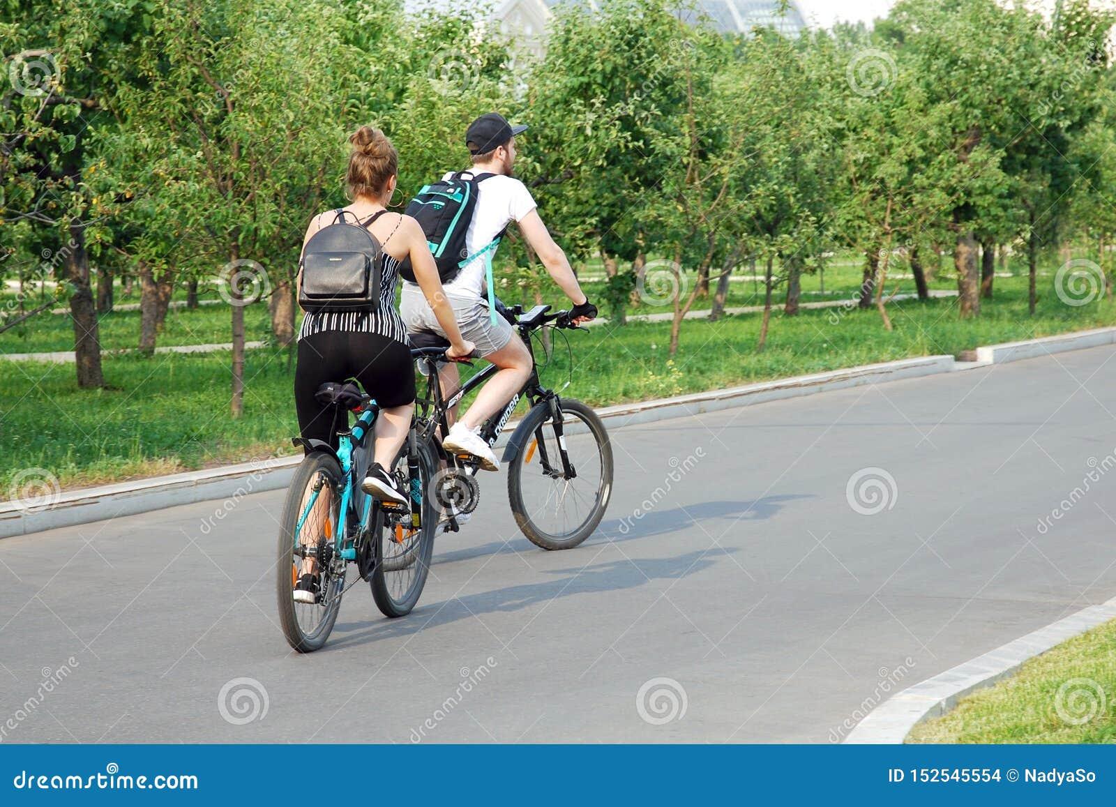 Велосипеды молодых пар ехать в парке лета