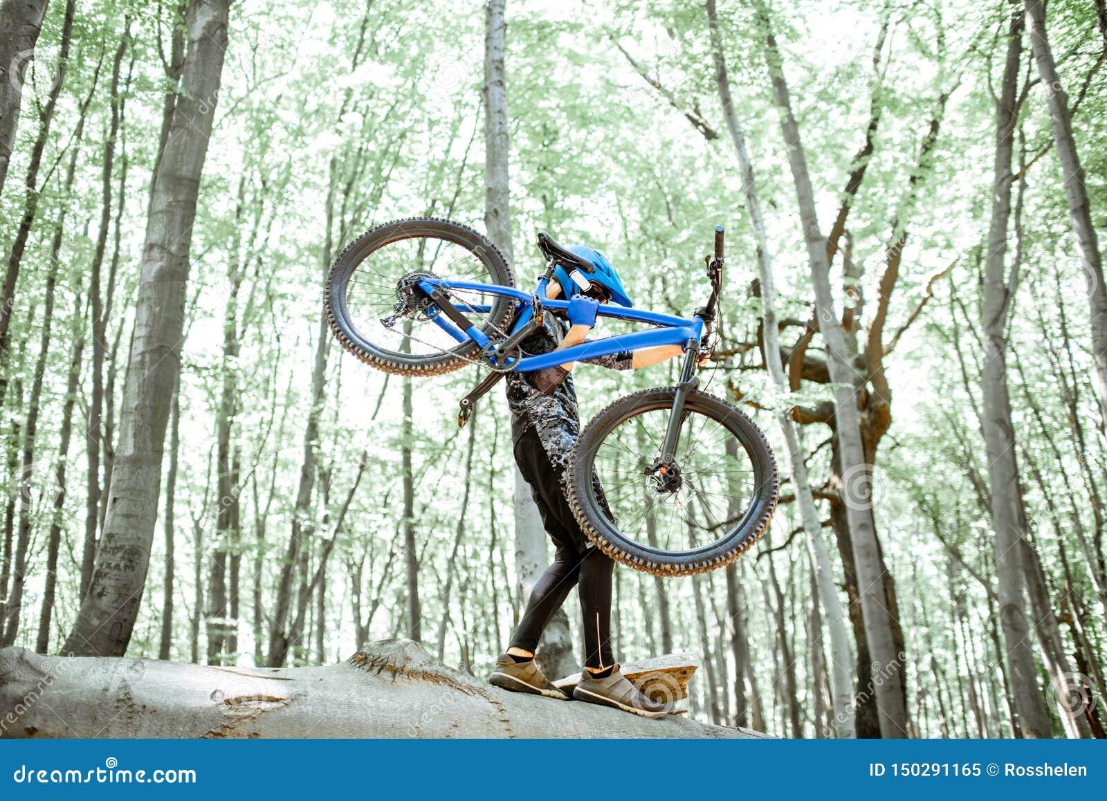 Велосипед нося велосипедиста пока едущ весьма в лесе