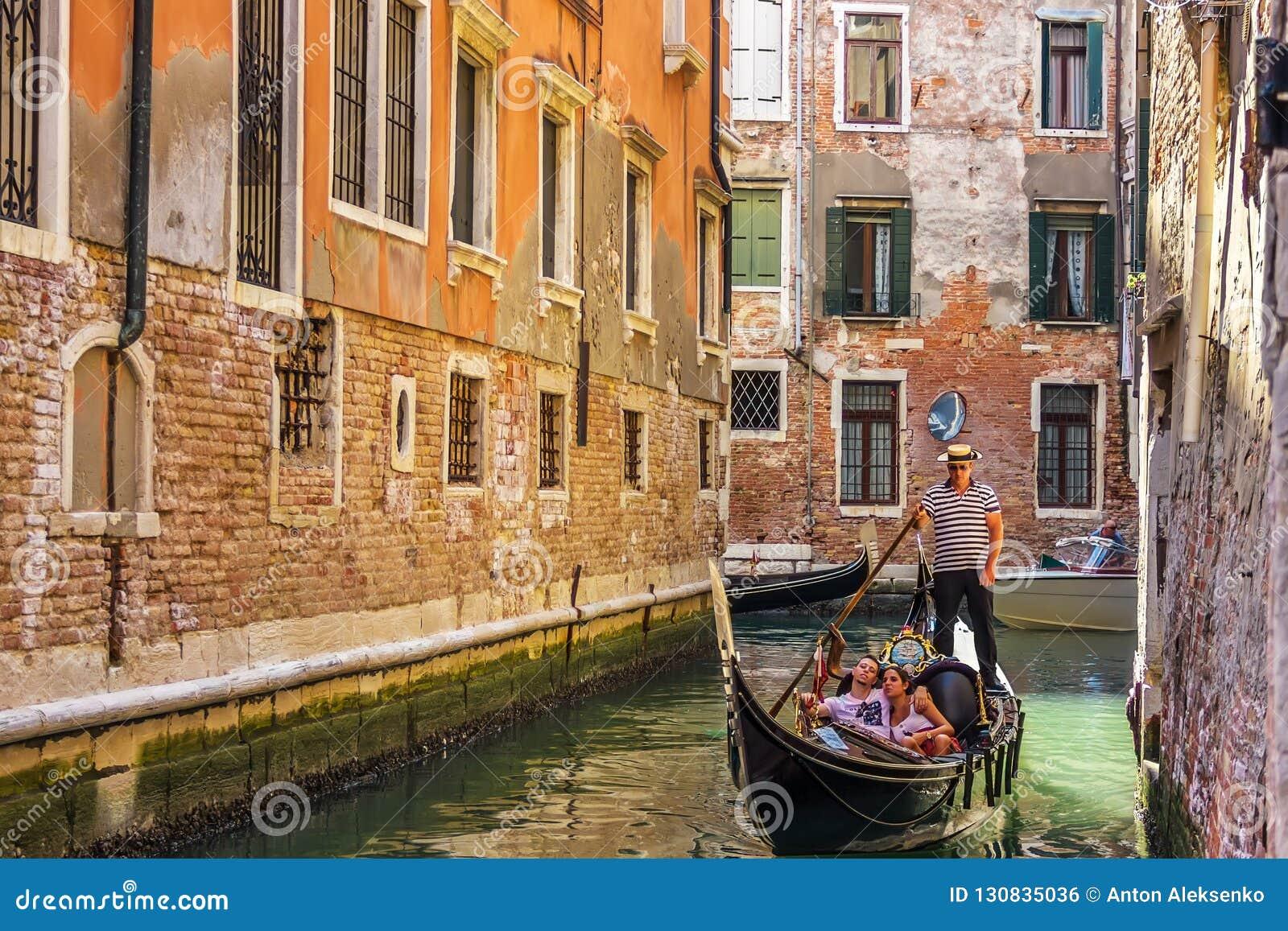 Венеция, Италия - 22-ое августа 2018: Гондола управляла gondolier в канале узкой улочки Венеции