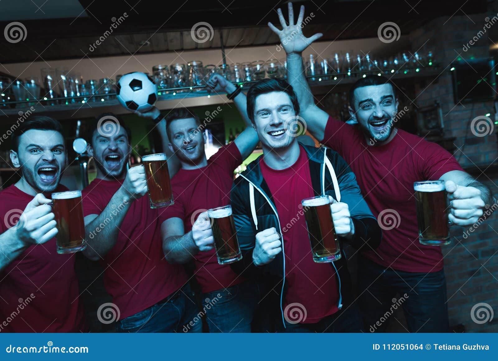 Вентиляторы спорт празднуя и веселя перед пивом ТВ выпивая на баре спорт