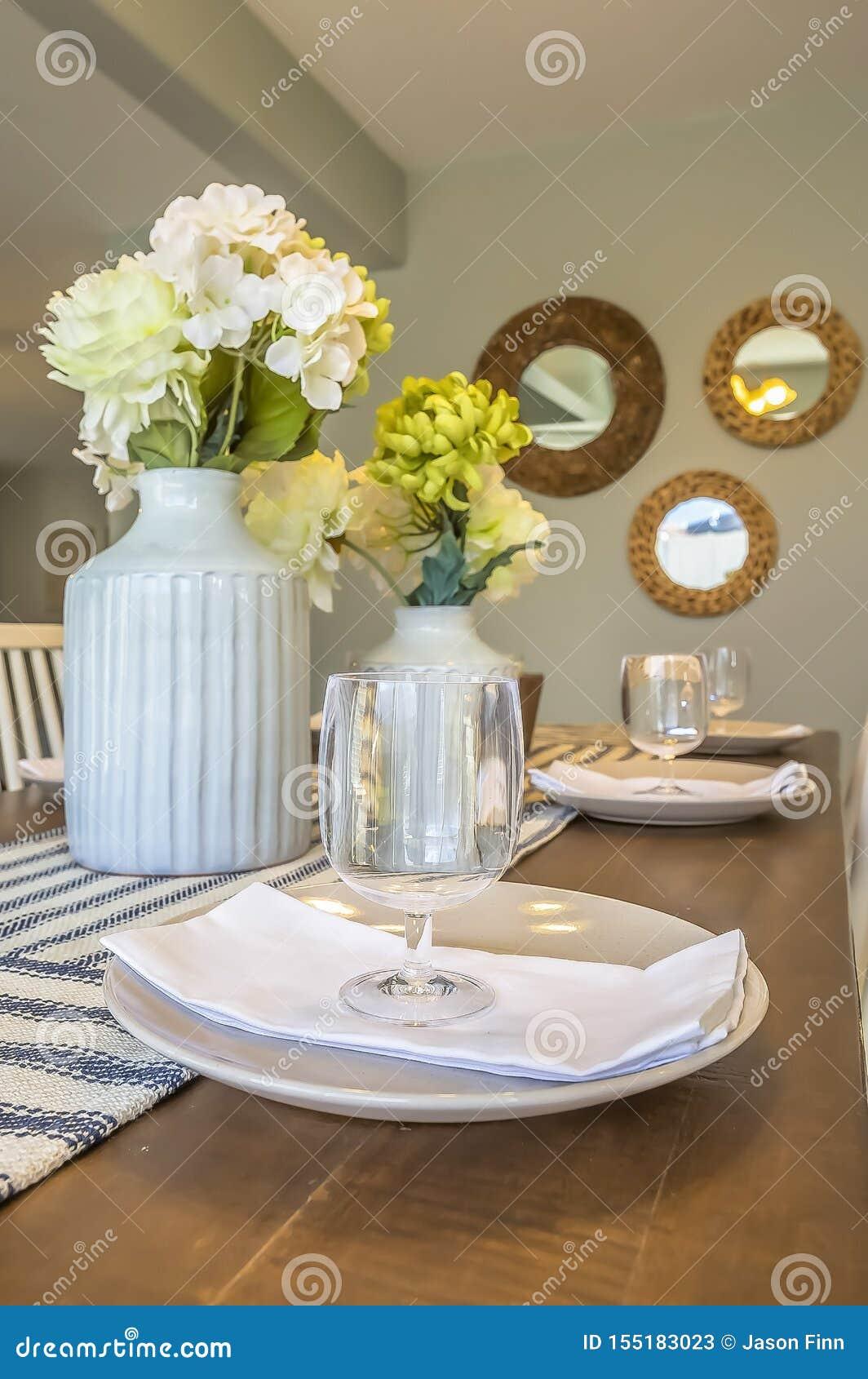 Вертикальная установка обедающего рамки внутри столовой дома с зеркалами и предпосылкой стены