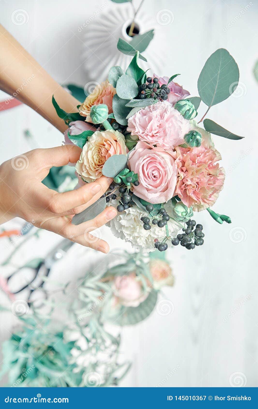 Вертикальное изображение женского флориста на работе Аранжировать различные цветки в букете r Учитель floristry в мастерских клас