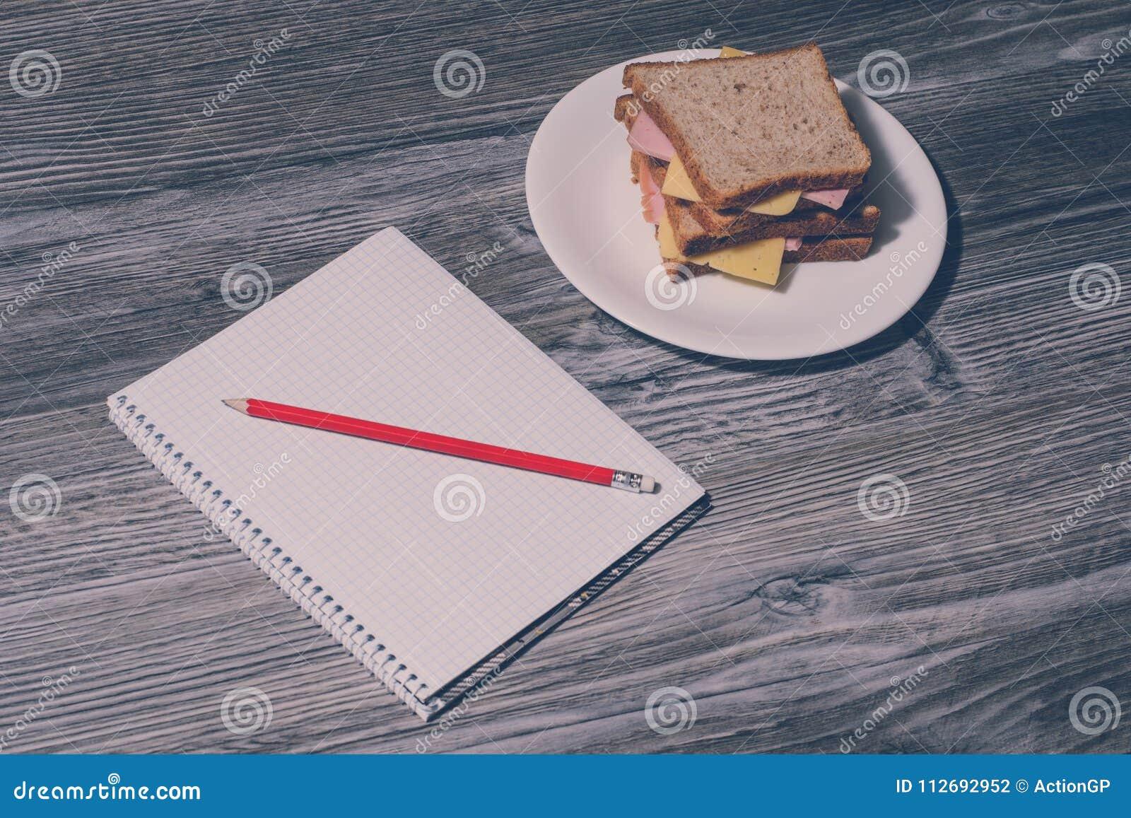 Верхняя часть над концом накладных расходов вверх по фото взгляда обеда на работе Вертикальный взгляд на тетради и карандаше, вку