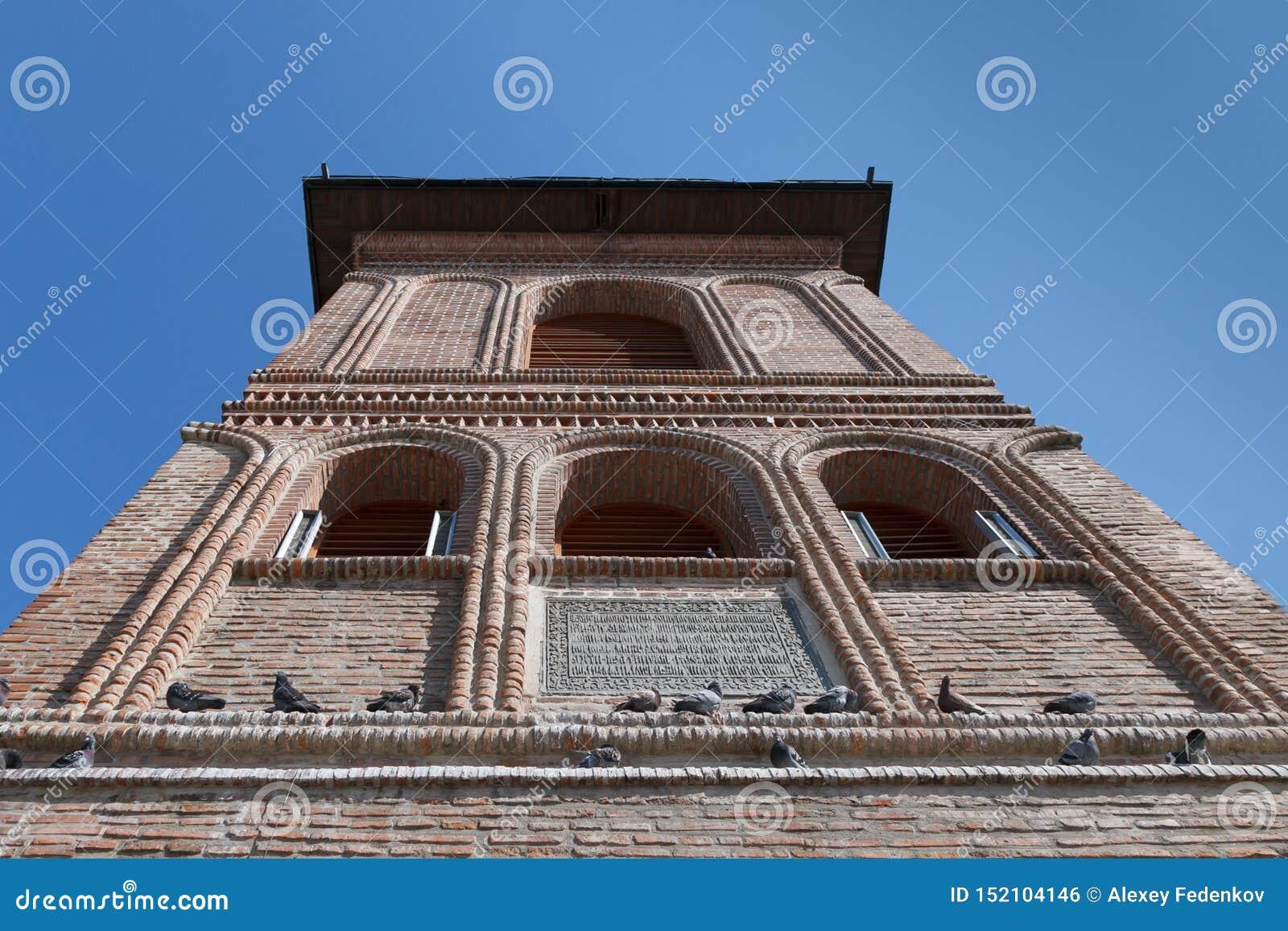 Верхняя часть старого фасада кирпича колокольни с сидя голубями Столичный холм, Бухарест, Румыния