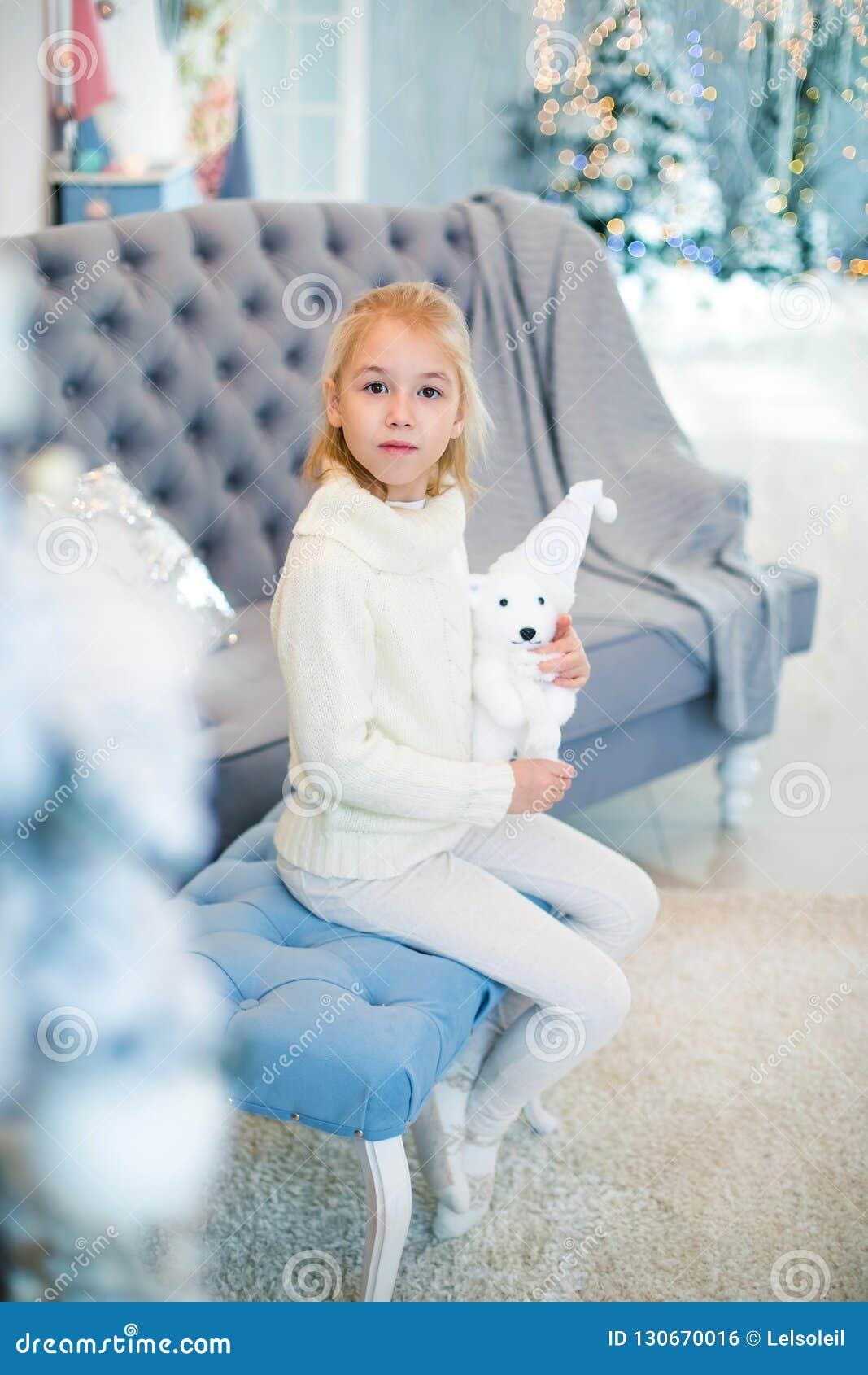 Веселое рождество и С Новым Годом!! Очаровывая маленькая белокурая девушка в белом теплом свитере с медведем игрушки сидя на голу