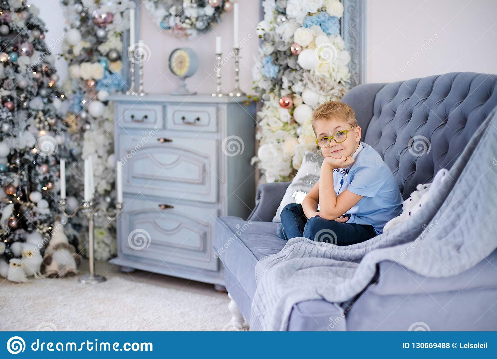 Веселое рождество и С Новым Годом!! Очаровывая маленький белокурый мальчик в голубой рубашке с большими стеклами сидя на софе око