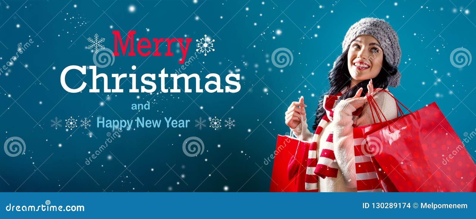 Веселое рождество и С Новым Годом! сообщение с женщиной держа хозяйственные сумки