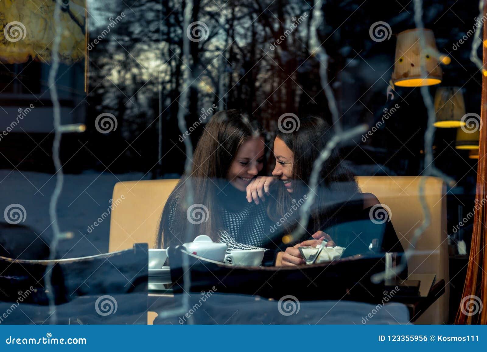 Веселые подруги, встречающ в кафе, снимая позади